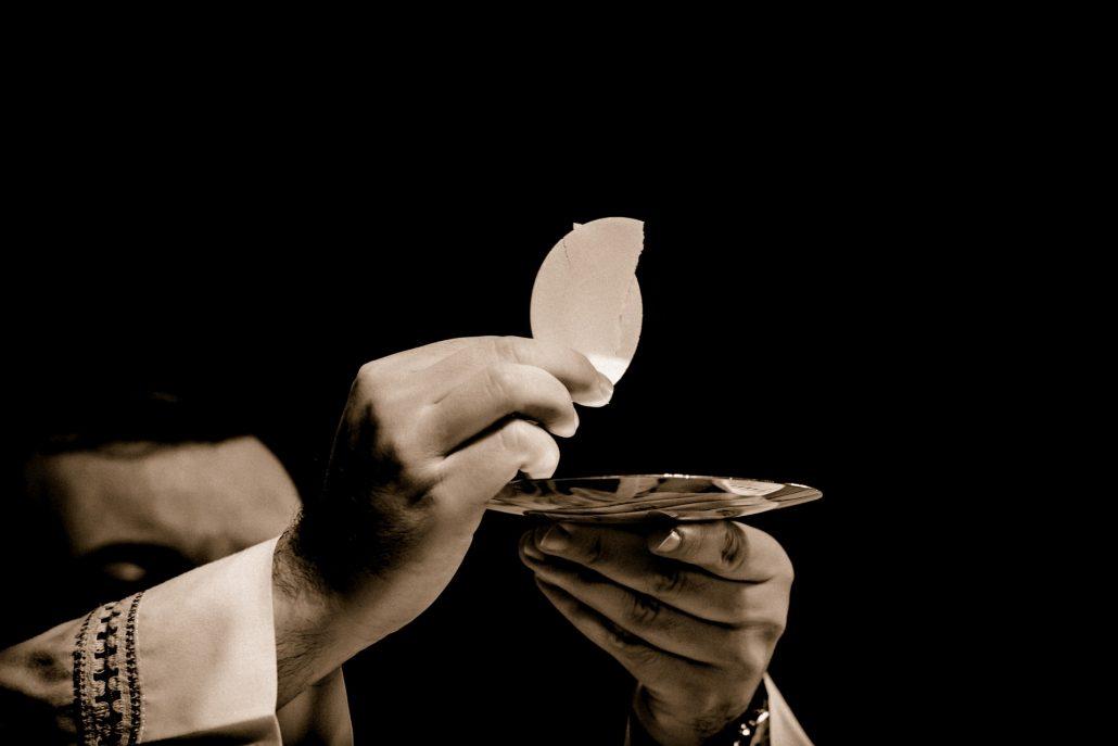 ceremonia de un párroco ofreciendo la comunión